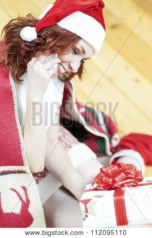 Christmas And New Year Ideas And Concepts. Smiling Caucasian Red-haired Santa Girl Holding Present B