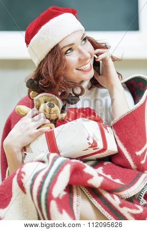 Positively Looking Expressive Red-haired Caucasian Santa Helper Girl With Small Christmas Gift. Talk
