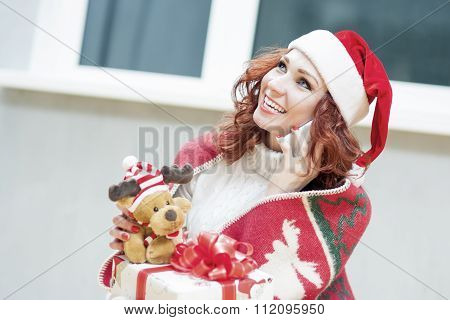 Positively Looking Expressive Red-haired Caucasian Santa Helper Girl With Christmas Gift Box. Speaki