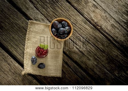 Burlap Sac Lying Over Rustic Textured Wooden Desk With Glass Jar Full Of Jam, Ripe Plums And Bowl Of