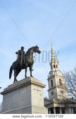 Statue of King George IV in Trafalgar Square with Saint Martin in the Fields church in the background.