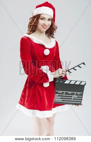 Portrait Of Sexy Female Santa Girl With Clapperboard Posing Against White Background