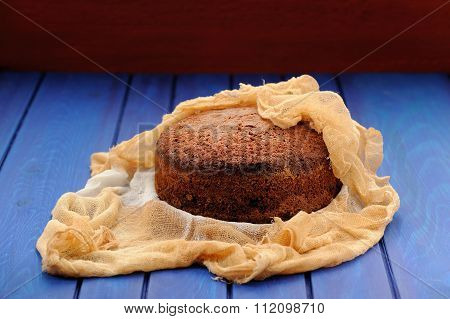 Homemade Chocolate Fruit Christmas Cake In Cheesecloth On Blue Table
