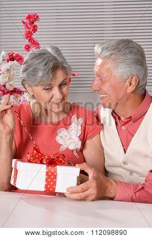 happy senior couple with gift