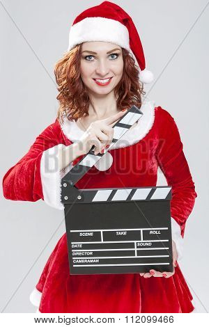 Female Santa Helper Holding Clapperboard In Front Ready To Set Off Filming. Against White Background