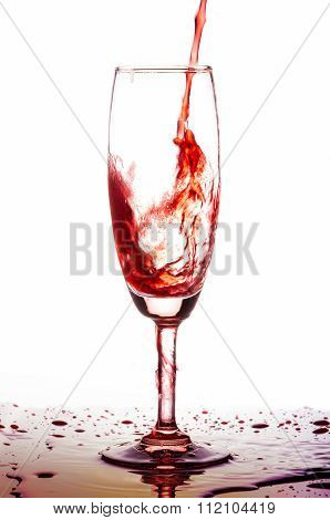 Red wine poured in a glass on white backgroubd.