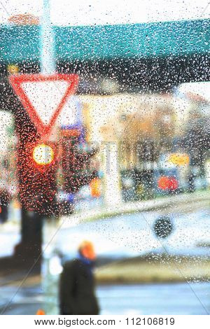 Blurred background of street life with traffic light and sign on rainy day. Man is waiting to cross