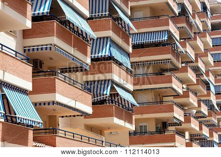 Facade of apartment building with balconies and awnings from the sun.