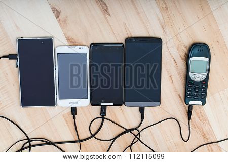 four smartphones and one classic phone connected to chargers
