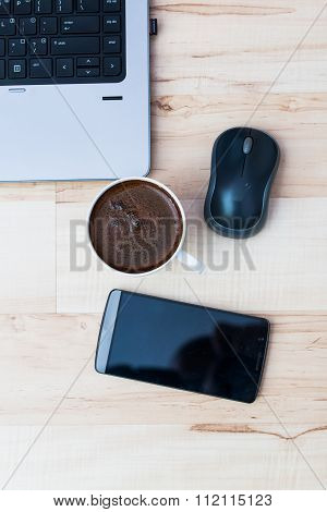 laptop smartphone mouse and coffee on a wooden floor