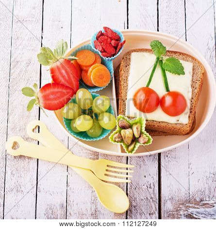 Lunch box for kids with fresh vegetables, fruits, nuts, berries