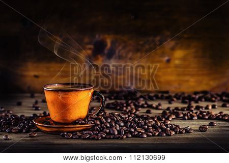 Cup of black coffee and spilled coffee beans. Coffee break.