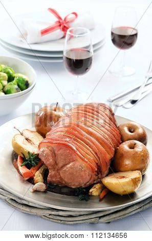 Christmas table setting with pork roast main centerpiece, baked apples, vegetable sides and wine