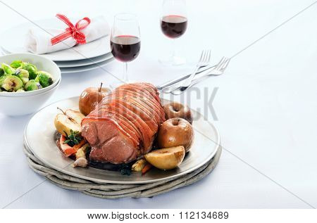 Thanksgiving table setting with pork roast, baked apples, vegetable sides and wine