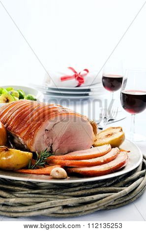 Sliced pork roast served at a table set with vegetable sides, wine and cutlery, plenty of copy space