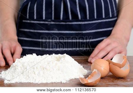 Close up of chef's hands with plain flour well and eggs in preparation process for baking, cooking, pastry making