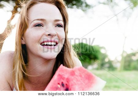 Cute girl lying down and eating slice of juicy red watermelon outdoors in park, lots of copy space