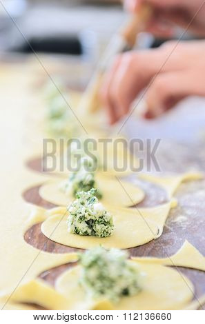 Pair of hands filling tortellini or ravioli with ricotta and spinach herb stuffing
