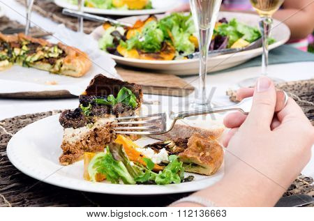 Anonymous female hand holding a fork in front of a plate of food, in a a casual outdoor dining party setting with other friends and platters of food