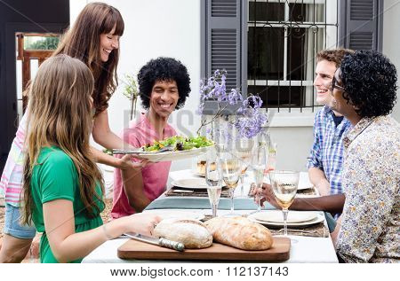 Serving appetisers to multi racial friends at a casual lunch gathering