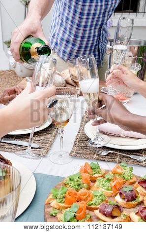 Group of diverse friends celebrating toasting with champagne at an outdoor garden party