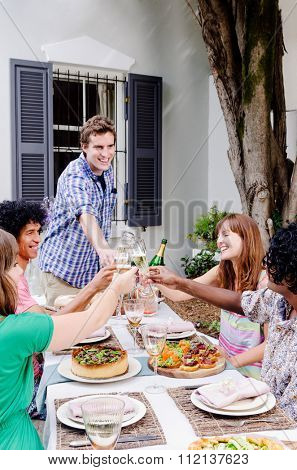 Group of diverse ethnic friends having fun celebrating toasting with champagne at an outdoor garden party