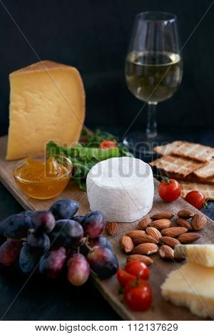 Cheese tasting platter with hard, soft, white rind assorted cheese, jam, grapes, raw almonds, cherry tomatoes, crackers and wine, perfect party entertaining gourmet food