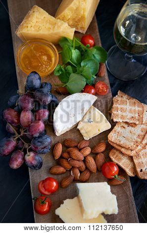 Cheese and wine tasting platter with variety of cheeses, jam, grapes, raw almonds, cherry tomatoes, crackers, luxurious party entertaining gourmet food