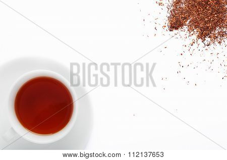 Cup of south african rooibos tea, healthy non caffeine detoxing drink with loose scattered leaves