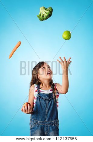 Young cute girl juggling vegetables and fruit over her head, healthy lifestyle, eating and diet concept