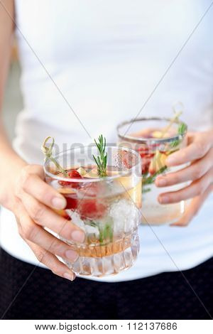 Anonymous woman holding two fruity cocktails with fresh fruit raspberry and rosemary garnish