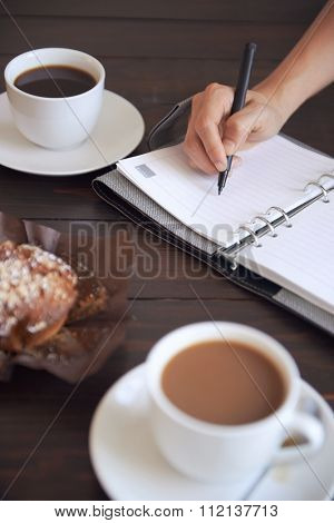 Cups of coffee with a muffin and a  person writing in her diary