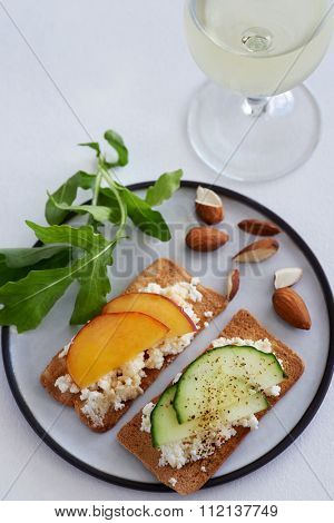 Party canapes snacks ricotta cottage cheese with sliced nectarine and cucumber and a glass of wine