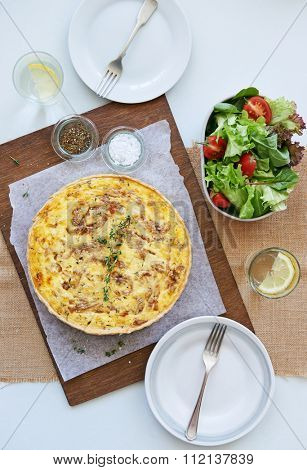Baked quiche tart frittata with caramelised onions and cheese served with a side green salad