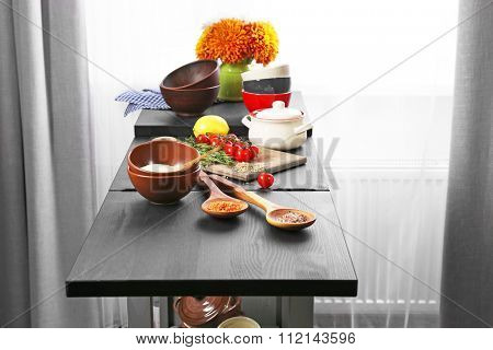 Colourful tableware with products on kitchen table