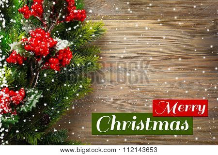 Christmas fir tree branches with rowan on wooden table