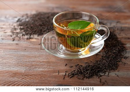 Glass cup of tea with green leaves on wooden background decorated with scattered tea