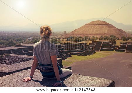 Young Woman Sitting On The Top Of Pyramid Overlooking Teotihuacan On A Sunny Day