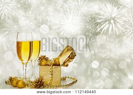 Glasses with champagne and golden gift box with Christmas balls against fireworks and holiday lights
