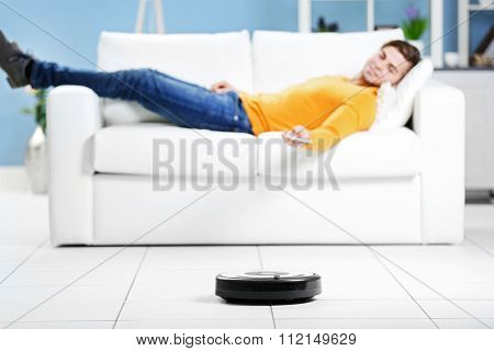 Cleaning concept - automatic robotic hoover clean the room while man relaxing, close up