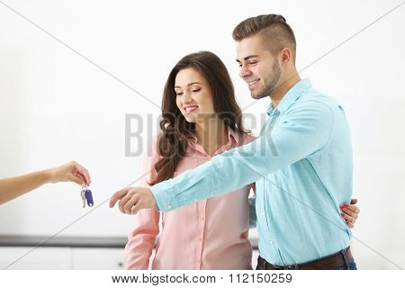 Hands of estate agent giving keys to  couple, on light background
