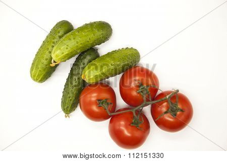 Fresh branch of red Sicilian ripe tomatoes and cucumbers on a white background.