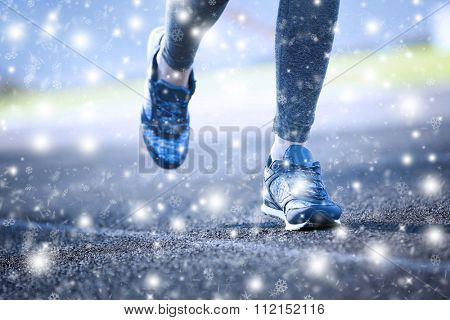 Sports woman legs in running movement over snow effect