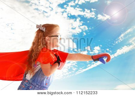 Fancy superhero girl with boxing gloves on sky background