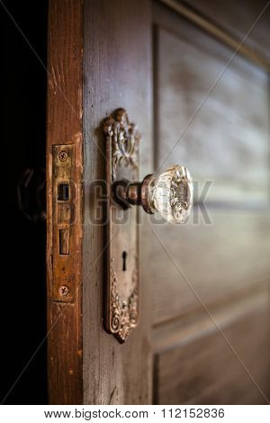An old door open with an ornate door knob.