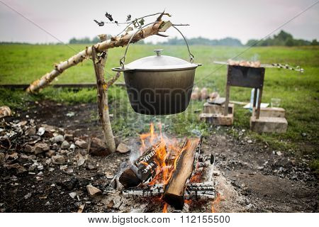 A cooking fish soup in pot on bonfire.
