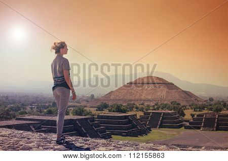 Young Woman Standing On Top Of Pyramid And Overlooking Teotihuacan In Orange Sunset Light