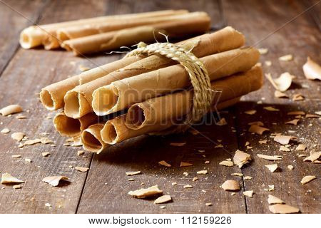some homemade neulas, typical thin biscuit rolls eaten in Christmas in Catalonia, Spain, tied with a string, on a rustic wooden surface