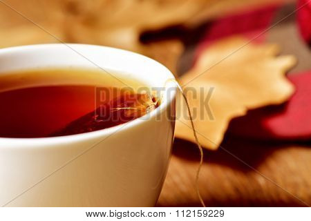 closeup of a white ceramic cup with a bag of tea or herbal tea being soaked in hot water, on a rustic wooden table