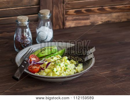 Healthy Breakfast Or Snack - Eggs Scramble, Avocado And Cherry Tomatoes On A Brown Wooden Surface